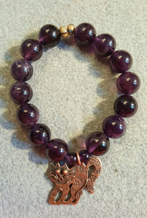 Request a custom order and have something made just for you. This seller usually responds within 24 hours. Large Amethyst beads, bronze double sided carved cat charm, Czech beads on elastic