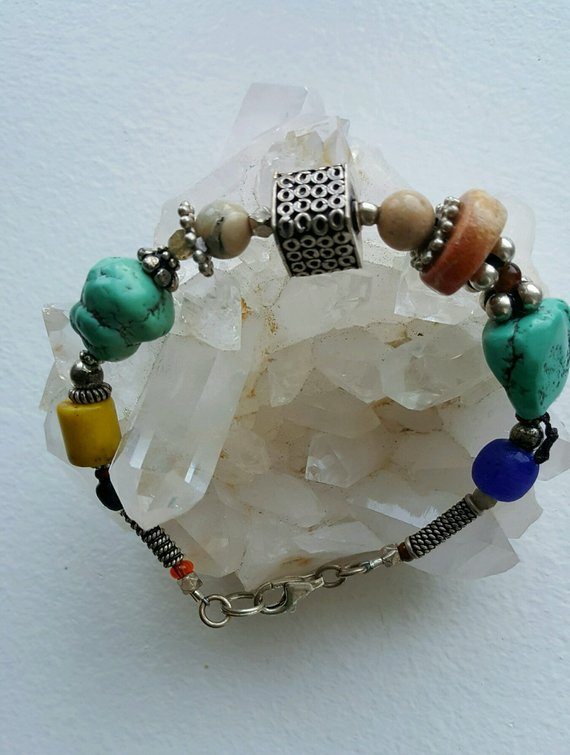 Lovely bracelet with turquoise chunks, large center decorative sterling bead, multi stones with lobster clasp