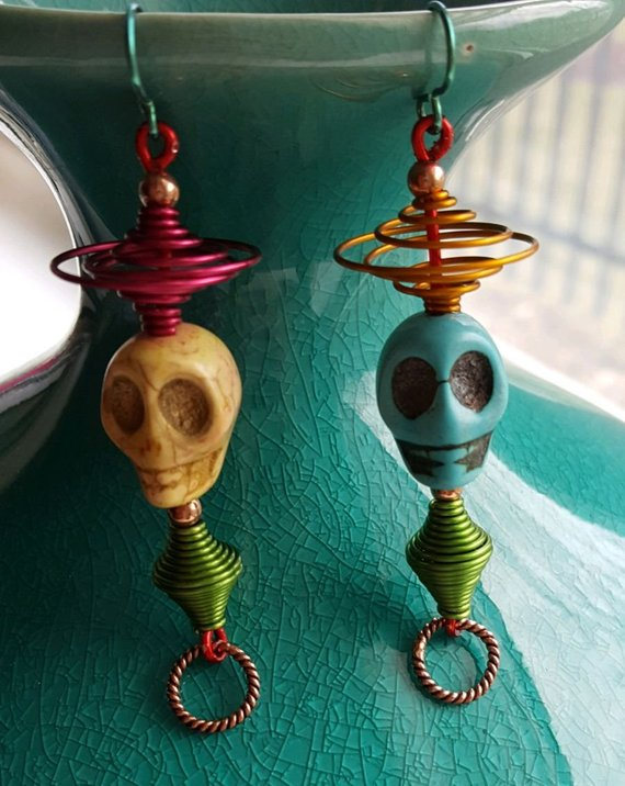 Crazy fun, mismatched Howlite skulls, on red wire, copper beads, multi colored aluminum swirls and ear wires