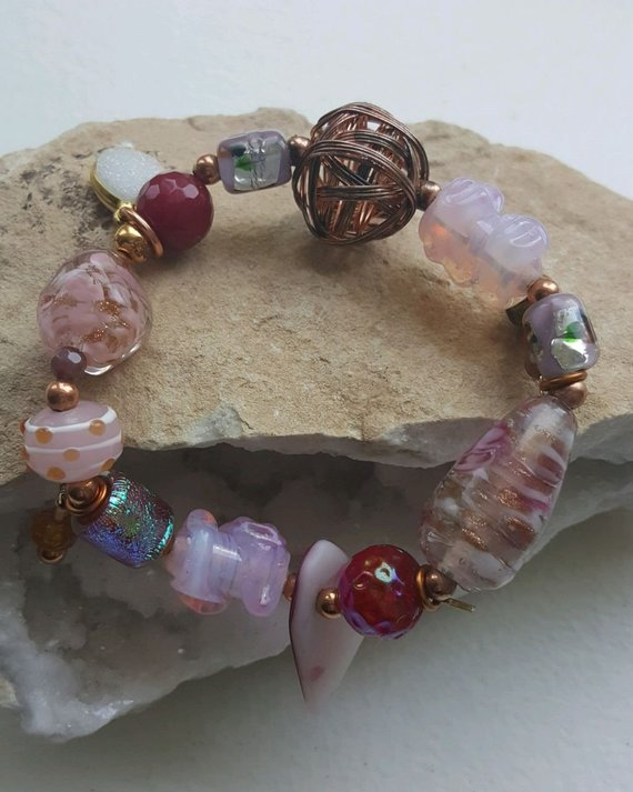 VERY pink glass beads, some with gold inside, copper beads, dichroic glass and iridescent beads, copper woven open beads, charms, on elastic