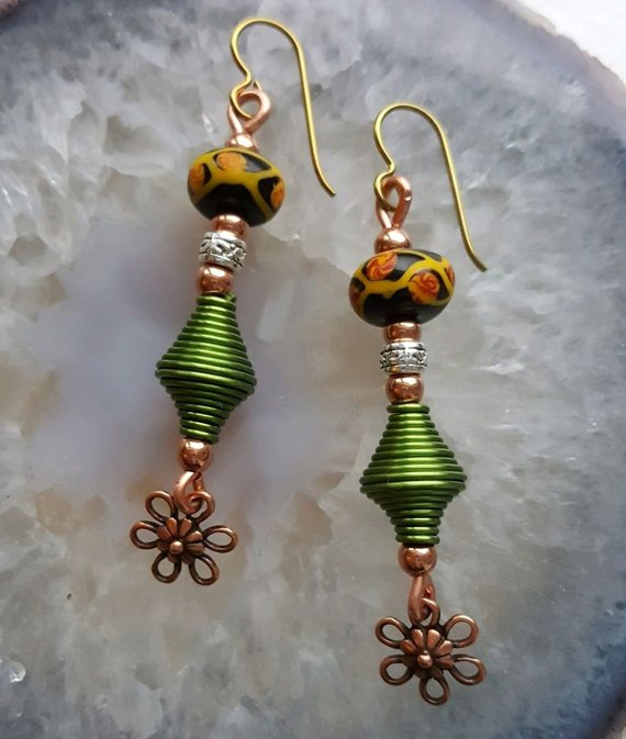 Green aluminum swirl beads on copper wire, copper flower drops, sterling beads, black and orange glass beads, on gold titanium wires