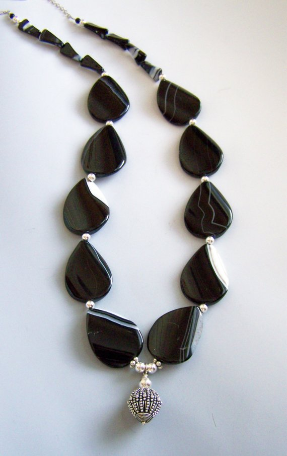 Beautiful black with small white coloration of these onyx beads, sterling center dangle