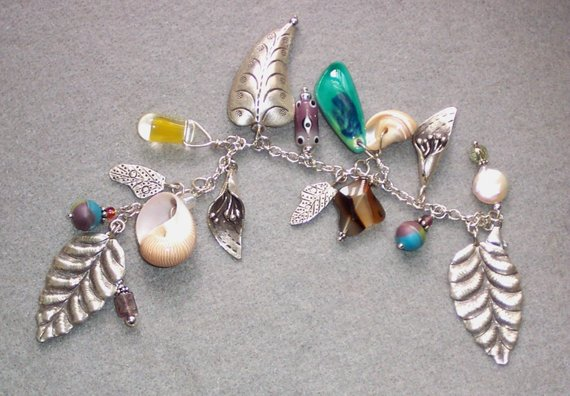 Sterling charm bracelet with large leaves and puff leaf, glass and ceramic and shell charms
