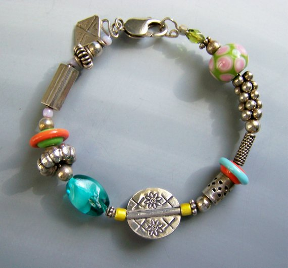 Sterling bangle on wire, carved sterling beads, colorful glass beads, large lobster clasp. One charm
